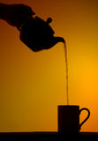 High Tea Silhouette. Silhouette of tea being poured from a pot into a mug Stock Images