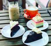 High tea time. Ice coffee, latte, rainbow cake , red velvet cheese cake & black forest cake Royalty Free Stock Image