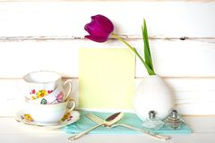 High Tea Time with Stack of Colorful Teacups, Purple Tulip in Vase, fork and spoon, with light green menu card on White Wood Board