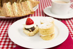 High tea. A traditional British high tea or afternoon tea served with tea cakes and sandwiches Stock Photography
