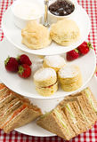 High tea. A traditional British high tea or afternoon tea served with tea cakes and sandwiches Stock Photo