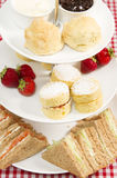 High tea. A traditional British high tea or afternoon tea served with tea cakes and sandwiches Stock Image