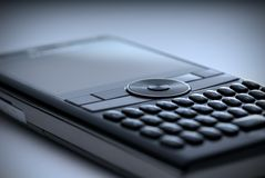 High tech cell phone - blue. Shallow focus closeup of a high tech compact Smart Phone in a blue tint royalty free stock photo