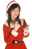 High Tech Santarina. A cute asian girl dressed as santa checks her list on a personal handheld computer royalty free stock images