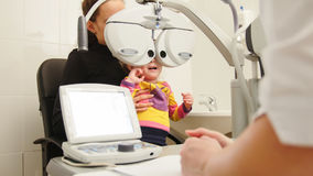 High tehnology in medicine - optometrist in clinic checking little girl`s vision - children`s ophthalmology Royalty Free Stock Images