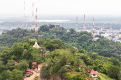 High telecommunications tower. Mounted on top of a mountain in the city, which is near the temple Royalty Free Stock Photos