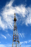 High television tower. The high television tower rises against the blue sky and white clouds Stock Photography