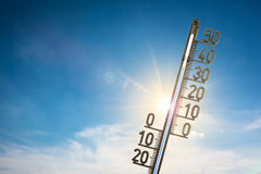 High temperature concept. Temperature concept - a blue sky with the sun shining from behind wispy clouds, a large thermometer in the foreground showing a Stock Photos