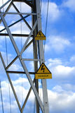 High tension. Danger signal of high tension, over blue sky Royalty Free Stock Photography