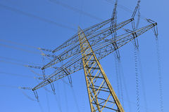 High tension electrical power. Low angle view of high tension electrical power lines and pylon tower Stock Image