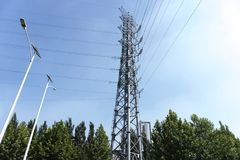 High tension line. High tension tower wires create symmetric pattern in bright, blue sky Royalty Free Stock Photos