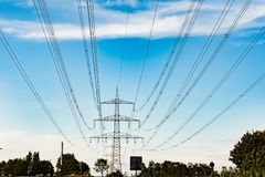 High-tension power line in blue sky with clouds. Transmission lines, Electricity pylon. High-voltage power line. High tension power lines towards blue sky with royalty free stock photography