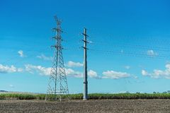 High Tension Power Poles In Rural Setting. High tension power poles against a background of blue sky and an agricultural field of sugar cane royalty free stock image