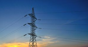 High tension pylon on intense sky during sunrise Stock Images