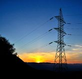 High tension pylon during sunrise. High tension pylon on splendid sky of colors during sunrise Royalty Free Stock Photos