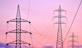 High tension pylons and hanging cables with colored sky Stock Image