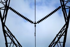 High tension symmetry. High tension power line silohouetted against a blue sky Royalty Free Stock Photos