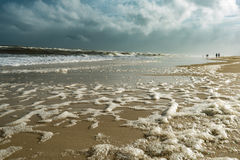 High Tide Beach Foam Seaspray with People. High Tide Beach Foam Seaspray with family of people walking down beach. Dramatic storm clouds looming. Extra room for Stock Photo