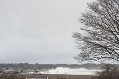 Deveraux Beach under Siege. High Tide has this raging storm and debris from the ocean. Rocks and ocean water are strong in the waves and cause damage to the stock photo