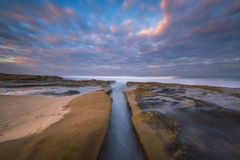 High tide rushing in a channel along the beach. Ocean water flowing up a channel in La Jolla, California at sunrise stock image