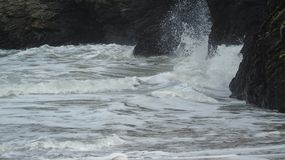 High tide. White high tide surf crashing against rocks Stock Image
