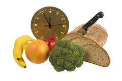 High time for diet. Loaf of bread with knife, broccoli, orange, peach, bananas and golden clock showing five minutes to twelve- symbolize the high time for Royalty Free Stock Image
