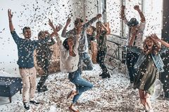 High time to party! Full length top view of happy young people g. Esturing and smiling while dancing with confetti flying everywhere stock photos