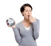 High time to sleep. Yawning woman and alarm clock Royalty Free Stock Image