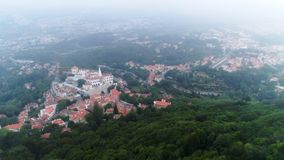 High top view Portugal town on slope in mist. Aerial view famous town of Sintra in mountains. Drone moving above treetops and rocks on slope showing scenic stock video