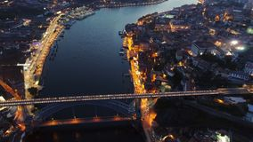 High top view above illuminated city in dusk. High top wide view dron rising over famous bridge Ponte de Dom Luis I and picturesque cityscape at dusk. Aerial stock video footage