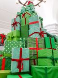High tower made from Christmas gift boxes covered in beautiful green paper with red ribbons in shopping mall hall. High tower made from Christmas gift boxes royalty free stock photo