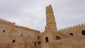High tower and national flag on top of fortress Ribat in Monastir, Tunisia. High tower and national flag on top of fortress Ribat in Monastir, Tunis. Ancient stock video footage