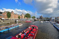 High traffic of passing boat canal Cruises filled with mass tourists on river canal with Amsterdam Central Station