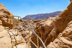 High trails secured by metal railings surrounded by caves, rocks, cliffs of ancient cooper mines canyons and mountains range in. Timna National Park in Israel royalty free stock photos