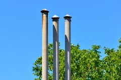 High triple chimney at the house next to the green trees.  royalty free stock photography
