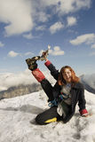 High up. Red haired girl cheering at the top of a high mountain with ice-axe in her hand royalty free stock photography