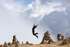 High up - Vitality. Young adult performs a jumping scene in front of a cloudy sky in the mountains of South Tyrol-Italy above some mystic & old stony sculptures stock photos