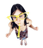 Party Girl. High and very wide angle full length view of an adult Caucasian black haired woman in her early 30's, wearing funky oversized spectacles and blowing Stock Images