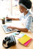 Female graphic designer using graphic tablet and laptop at desk. High view of African american female graphic designer using graphic tablet and laptop at desk in royalty free stock photos