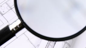 High view of magnifying glass over architecture plans stock video