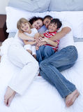 High view of parents and children relaxing in bed Stock Photo