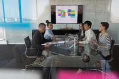 Business people having discussion in a meeting. High view of sitting mixed race business people having discussion in a meeting at modern office. They work hard royalty free stock photo