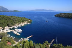 High view of Spartochori bay. Bay and yachts on pontoons in Meganissi, Greece. Distant mountains on mainland stock images