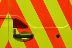 High visibility stripes on back of highway contractors van. Close up of high visibility stripes on back of highway contractors van around door handle and lock Stock Photography