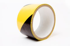 High visibility tape. Roll of yellow and black high visibility tape isolated against white background Royalty Free Stock Image
