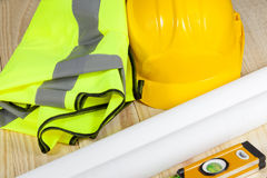 High visibility vest and hard hat laying on a wooden floor. High visibility vest laying on a wooden floor with a yellow hard hat and a spirit level Royalty Free Stock Images
