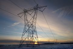 High volatge pylon at sunset in winter Royalty Free Stock Photo