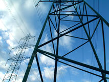 High voltage. Power poles in front of a cloudy blue sky Royalty Free Stock Image