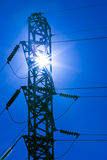 High Voltage. Rays of sun in pylon of electrical power transmission line on blue sky stock photos