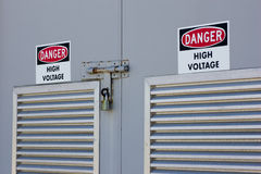 High Voltage area. A closeup of a set of locked, louvred, metal security doors, with high voltage stickers, indicating danger to anyone who opens them Royalty Free Stock Images